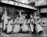 Manchu women of the Forbidden City or Gugong in Beijing pose for a photograph c. 1910 in the very last days of the Manchu Qing Dynasty (1644-1911). They wear elaborate and expensive dresses. Their faces are whitened with powder, and their lipstick is applied in a narrow band across the centre of their lips following the fashion of the time.