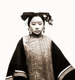 Example Of A Coiffure On A Tartar Or Manchu Female,  who is wearing a long sleeved quilted garment. The hair is wrapped around a flat strip of wood. Scottish photographer John Thomson.